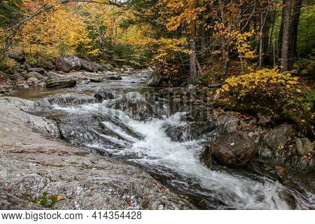 River cascades with stones and water in motion during autumn seasom