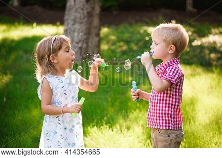 Five Years Old Caucasian Child Girl And Boy Blowing Soap Bubbles