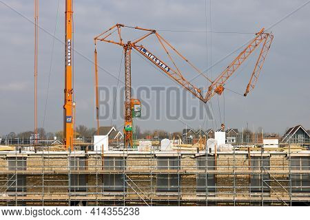 Urk, The Netherlands - March 25, 2021: Big Mobile Tower Cranes Raising At Construction Site Apartmen