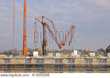 Urk, The Netherlands - March 25, 2021: Big Mobile Tower Cranes Fold Up At Construction Site Apartmen