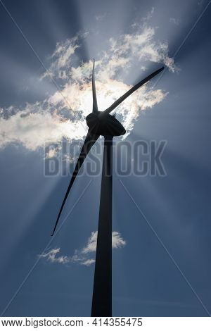 Silhouette Windturbine With Backlight And Sunrays, The Sun Is Hidden Behind The Motor Housing