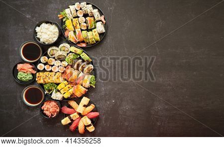 Assorted sushi set served on dark dark background. Top view of seafood, various maki rolls