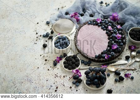 Homemade blackberry tart. Sweet pie with blackberrym blueberry and grapes on stone table