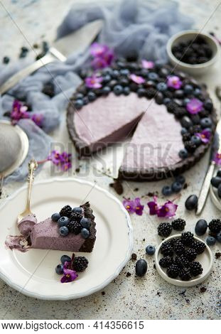 Plate with homemade piece of delicious blueberry, blackberry and grape pie or tart served on table