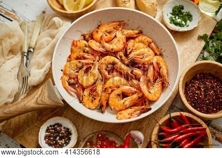 Roasted Prawns on frying pan served on white wooden cutting board