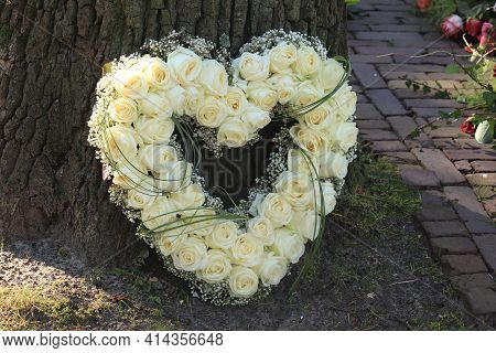 A Sympathy Flower Arrangement In A Heart Shape, White Roses