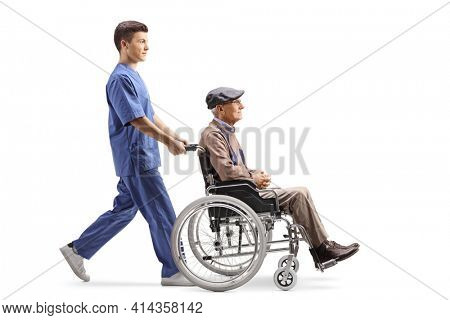 Full length profile shot of a male nurse pushing a elderly man in a wheelchair isolated on white background
