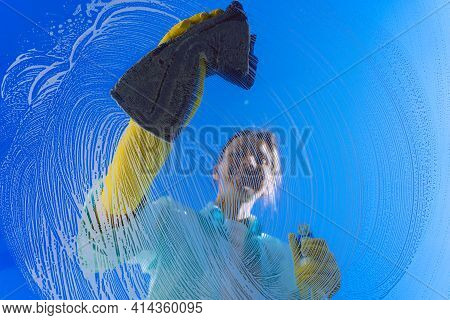 Smiling Woman In Yellow Gloves Cleaning Window Glass With Rag On A Blue Sky Background On A Sunny Su
