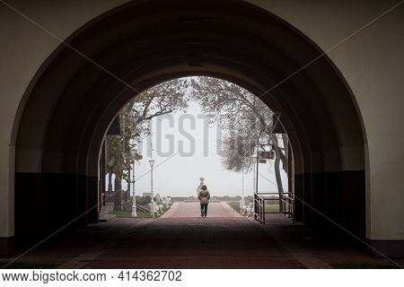 Palic, Serbia - November 18, 2020: Woman Walking Alone On An Alley Of Park Heroja During An Autumn F
