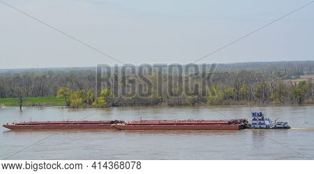 A Tug Boat Is Pushing Barges Down The Mississippi River Past Natchez, Mississippi