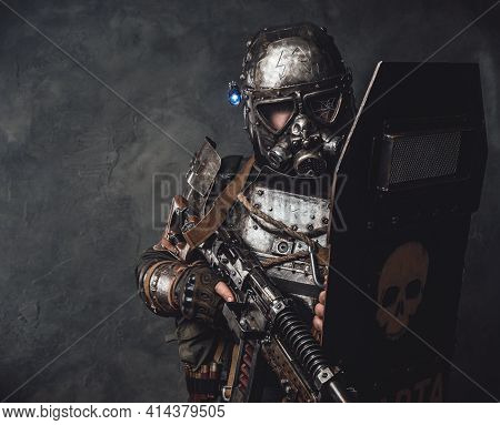 Military Stalker With Shield And Gun In Dark Background