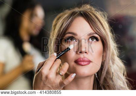 Makeup Artist Applying Corrector On Flawless Fresh Skin Doing Make Up. Female Eye With Long False Ey