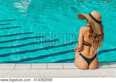 Girl By Pool. Happy Young Sexy Woman In Bikini Swimsuit, Sunglasses And Straw Hat Relaxing In Blue W
