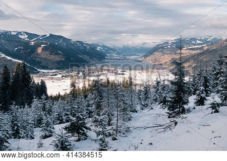 Zell Am See With Zeller See Lake, An Alpine Winter Landscape With Snow Covered Mountains In Salzburg