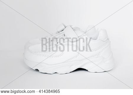 Isolated White Childrens Leather Sneakers In A Minimalistic Style On A White Background, Concept Of