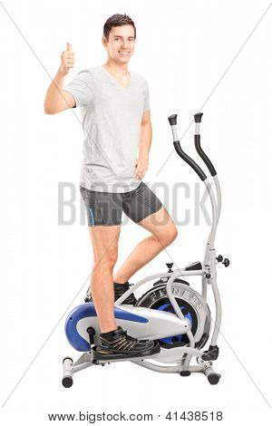 Full length portrait of a young man exercising on a cross trainer machine and giving thumb up isolated on white