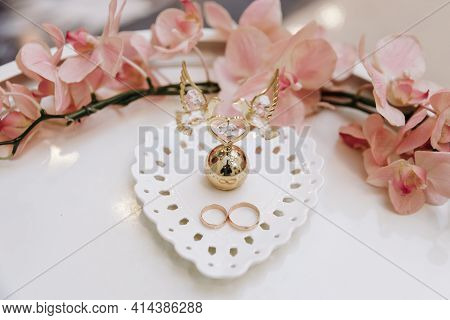 Wedding Day. Gold Wedding Rings On A White Saucer On The Table, Flower Decorations, Solemn Ceremony