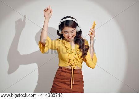 Cute Young Woman Texting On Her Phone While Listening Music, While Listening Music On White Backgrou