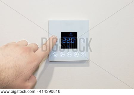Close-up Of A Caucasian Male's Hand Adjusting A Modern Wall-mounted Digital Thermostat.