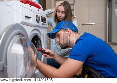 Repairman Repairs A Washing Machine In Front Of A Woman. A Man Communicates With The Owner Of A Wash