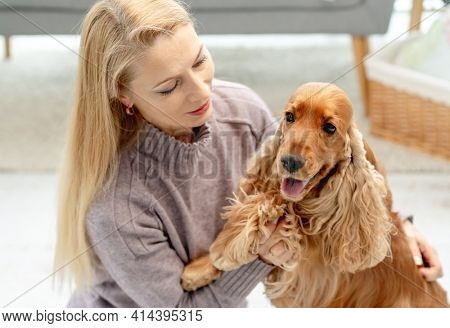 English cocker spaniel dog with loving woman owner sitting on floor at home