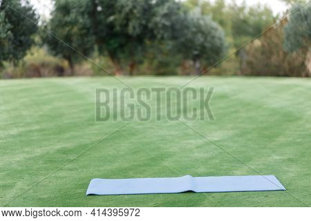 Yoga Or Fitness Mat. Mat For Sports On The Green Grass In The Park. Exercise In The Fresh Airyoga Or