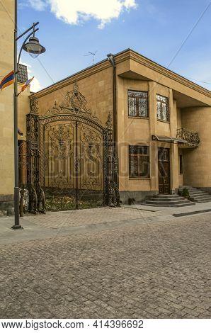 Gyumri,armenia,05 September,2019:wrought Iron Gate With Monogram Near A Modern Building Of Light Tuf