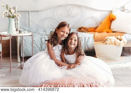 Two Cute Girls Cuddle In A Light Room. Smiling Children Sitting Together In Bedroom Looking In Camer