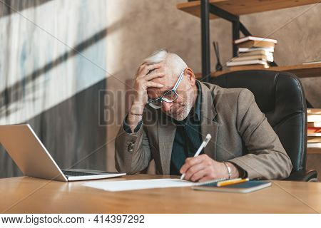 Sign A Will. The Senior Man Clings To His Head In Despair And Signs The Document. Financial Problems
