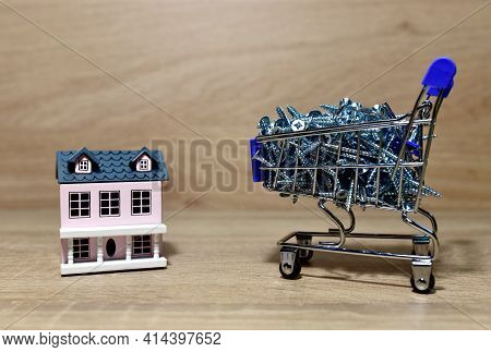 Self-tapping Screws In A Shopping Cart And House On Wood Background. Screw For Working With Wood Pro