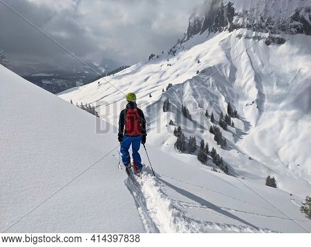 Skier Draws His Own Track Through The Powder Snow. Freeride In The Mountains Of Glarus On The Silber