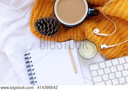 Coffee, Clean Notebook. Keyboard, Cone , Candle, Earpods On White Crumpled Sheets And Yellow Knitted