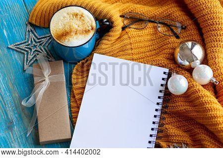 Winter Or Autumn Cozy Flat Lay Composition. Warm Knitted Sweater, Xmas Toys, Coffee, Cup And Blank P