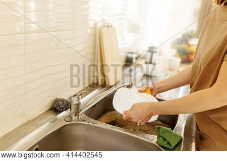 Young Woman Washing Dishes In The Kitchen Sink At Home, Close Up Of Hands With Sponge And Soap, Hous