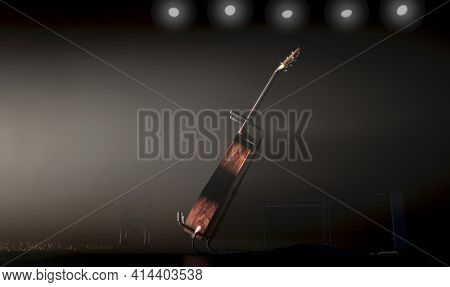 An Acoustic Guitar Resting On A Stand On A Music Concert Stage Lit By A Single Dramatic Spotlight Fa