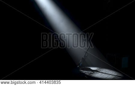 An Electric Guitar Resting On A Stand On A Music Concert Stage Lit By A Single Dramatic Spotlight On