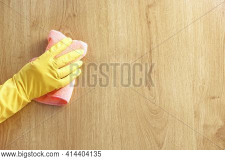 A Man's Hand In A Yellow Rubber Glove Oil Polishes The Wooden Surface Of The Table, The Floor With A