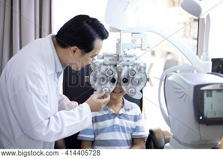 Asian Optometrists Are Examining Pediatric Patients' Eyes With The Autorefractor In A Clinic.