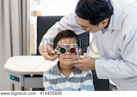 An Asian Optometrist Examines A Child's Eyesight Using A Trial Frame. The Boy Patient Visits An Opht