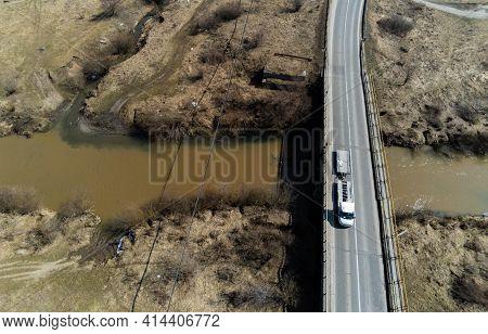 Miercurea Ciuc, Romania- 27 March 2021: Passing Cars On The Bridge Over The Dirty Olt River.
