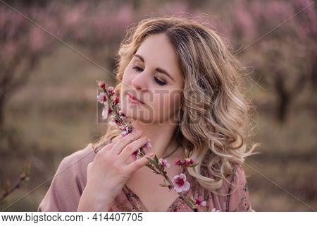 Tender Young Woman With Beautiful Curly Blonde Hair, With Clean Face, Natural Makeup, Stands In Bloo
