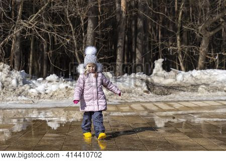 Sad Child Walks Through A Spring Puddle. Clothes Are Soaked