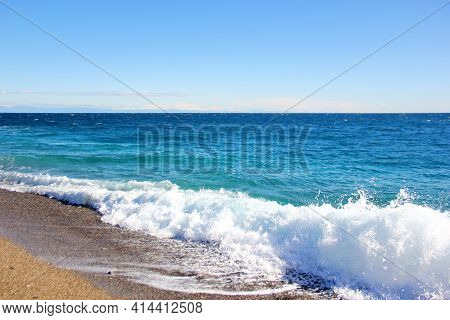 The Sea Wave Rushes To The Shore, Forming A White Foam, Clear Blue Water, Sand On The Beach, A Sunny
