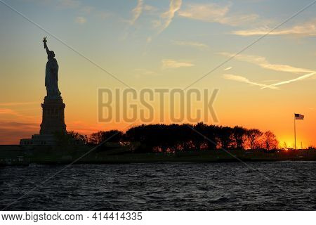 Statue of Liberty in silhouette at sunset viewed from the water with Flag, clouds and colorful sky.