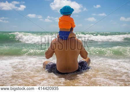Family Values Concept. Father Defender. The Baby Sits On Dad's Shoulders, Dad With Baby Sits On The