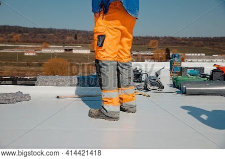 Roofer Man Works On A Flat Roof With Pvc Membrane Insulation System