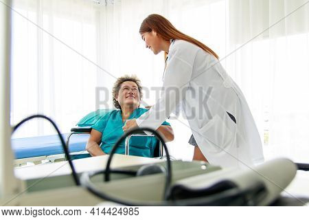 Asian Beautiful Woman Doctor Smiles And Makes Eye Contact With The Old Lady Patient. The Old Lady En