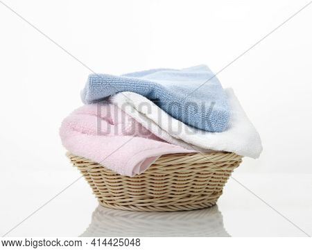 Folded Towels Stack In Basket On White Background,heap Of Colorful Laundry On Table.household,clean