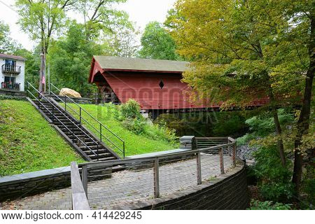 NEWFIELD, NEW YORK - SEPT 25, 2018: The Newfield Covered Bridge spans the Cayuga Inlet. Built in 1853, it is the oldest covered bridge in daily use in New York.