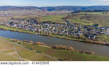 Aerial View Of The River Moselle Valley With The Village Brauneberg And Mountains In The Background